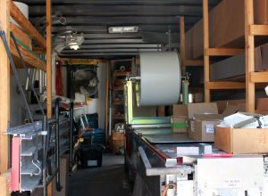 Inside of a stocked Naster Roofing seamless gutters fabrication truck